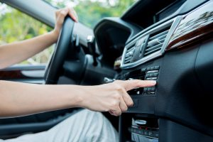 Woman sitting in a car and touch play finger in a auto smart system.